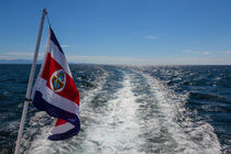 Flag at the back of a boat by Craig Lapsley
