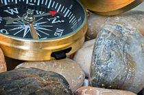 Navigation compass on stone pebbles by Serhii Zhukovskyi