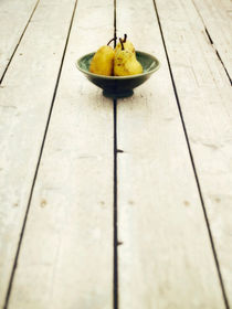 green bowl filled with yellow pears by Priska  Wettstein