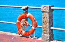 Rettungsring in leuchtendem Orange mit Kapitänsmütze von Gina Koch