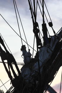 Young woman climbing in the rigging of a tall ship at dusk von Intensivelight Panorama-Edition