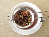 Kräutertee mit Früchten und Blüten im Teesieb von Heike Rau