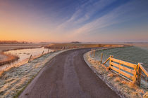 Typical Dutch landscape with a dike, in winter at sunrise by Sara Winter