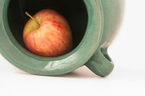 Close-up-view-of-a-red-apple-inside-the-greenish-earthen-jar