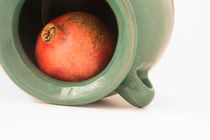 close up view of a red pomegranate inside the greenish earthen jar by Masoud Rezaeipoor