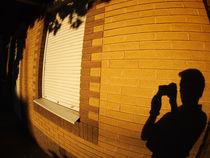 The shadow of a man on the illuminated wall of a house von Vladislav Romensky