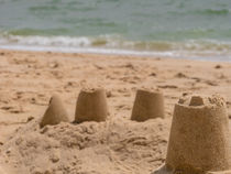 Sandcastle on the beach in the sand by nese