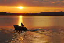 fisherman with motorboat at the lake in sunrise von Christian Zirsky