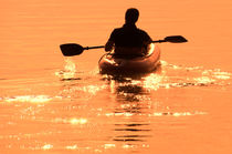 Man paddling with boat in the sunset von Christian Zirsky