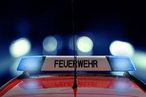 Feuerwehr Auto fährt im Dunkeln mit Blaulicht by fotowelt-luebeck
