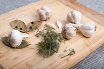 Wooden board with garlic and dried spices closeup by Vladislav Romensky
