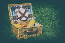 Picnic Basket With Orange Juice Bottle, Apples, Peaches, Oranges And Croissants On Green Grass In Spring by Radu Bercan