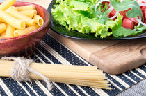 Diagonal composition on a table with a fresh salad, pasta and spaghetti for cooking  by Vladislav Romensky