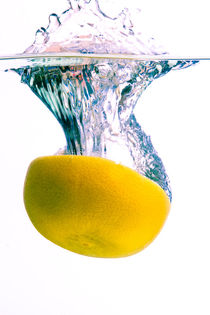 Grapefruit falls into water with big splash on white background by Sharon Yanai