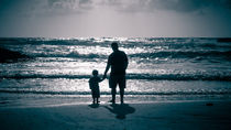 Father and Son on the beach at dusk von Sharon Yanai