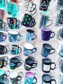 colorful mugs hanging on the white wall by timla