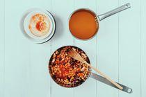 Preparing Chili Bean Stew On White Wood Kitchen Table von Radu Bercan