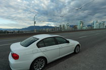 White car in front of the Skyline of Vancouver von stephiii