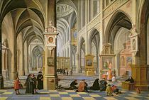 Church interior, with people at prayer in the foreground and a small procession in the main aisle