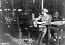 Woman broaching key seat in front sight carrier for rifle by American Photographer