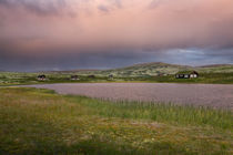 Huts on lake in landscape of Norway during sunset von Bastian Linder