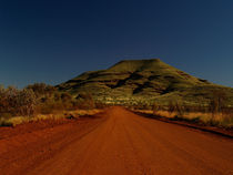 Australia dirt road with red sand in front of green hill von Bastian Linder