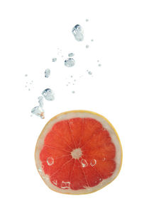 Grapefruit in water with air bubbles by Bastian Linder