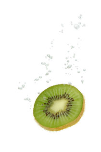 Kiwi fruit in water with air bubbles by Bastian Linder