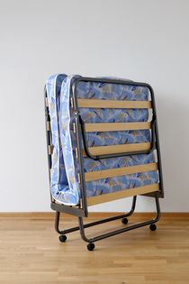 A folding bed in front of a white wall an a blue mattress von Marcus Krauß