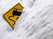 Slippery Road Sign in the Snowbank by Ed Book