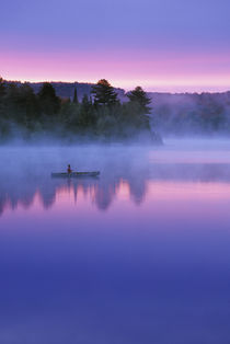 Canada, Ontario, Algonguin Park, Canoeist on lake at sunrise.   Credit as by Danita Delimont