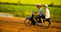 Girls Riding Along A Dirt Road In Cambodia. by Jason Friend