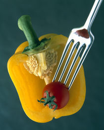 Close up of half yellow pepper with cherry tomato in center on fork tines by Panoramic Images