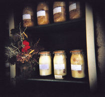Jars and flowers in racks von Panoramic Images