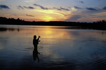 Fly-fisherman silhouetted by sunrise by Panoramic Images