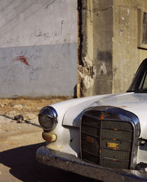 Rusty car in front of a building, Syria by Panoramic Images