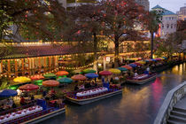 Restaurant along a river lit up at dusk by Panoramic Images