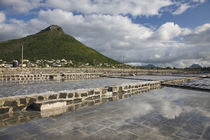 Salt ponds with a village and mountain in the background by Panoramic Images