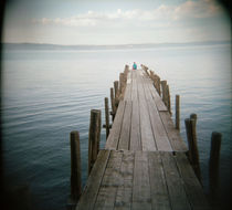 Person sitting on a pier, Lake Bolsena, Italy von Panoramic Images