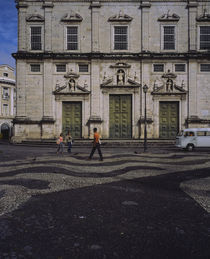 Three people walking in front of a building by Panoramic Images