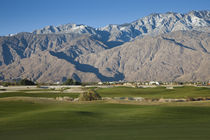 Golf course with mountain range by Panoramic Images