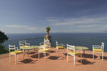 Empty tables and chairs on the balcony of a hotel by Panoramic Images