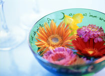 Pink, orange and yellow flowers floating in a blue bowl von Panoramic Images