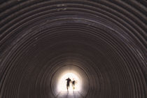 People hiking through underpass, Scotland. by Panoramic Images