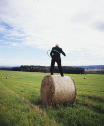 Rear view of a man standing on a hay bale playing with a plastic hoop, Germany von Panoramic Images