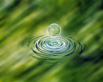 Clear bubble rising from ripples in mottled green water von Panoramic Images
