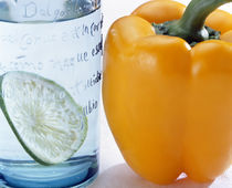 Close up of yellow pepper sitting beside blue glass with slice of lime by Panoramic Images