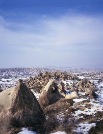 Cliff dwellings in a snow covered field by Panoramic Images