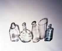 Three clear bottles one clear vase and one blue bottle standing side by side von Panoramic Images
