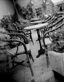 Empty chairs and tables in a sidewalk cafe von Panoramic Images